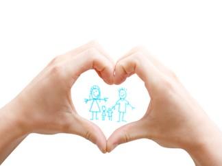 Hand making heart around family